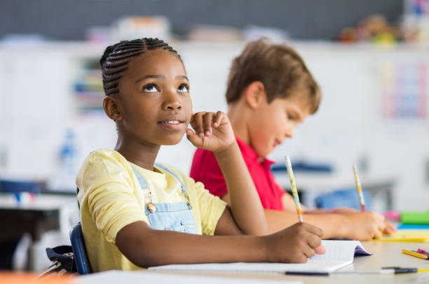 Thoughtful elementary school girl sitting at desk and looking up. Thoughtful schoolgirl looking up while sitting at desk during exam with classmate in background. Black scholar thinking about the solution of the exam.