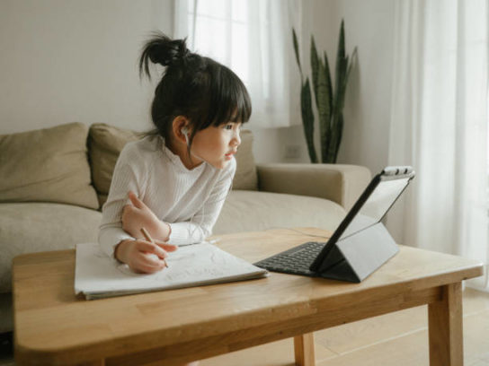 Asian daughter attending to online class from home.