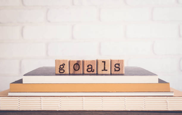 The word GOALS, alphabets on wooden rubber stamps on top of books with bricks background, blank copy space, vintage minimal style. Concepts of success, project planning and business management.